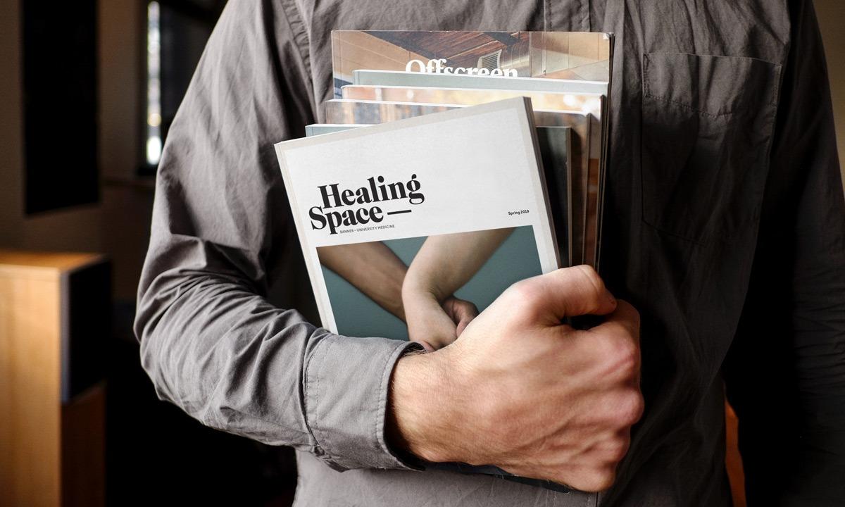 Man holding stack of magazines